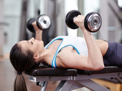 Young woman bench pressing with dumbbells in the gym, working triceps and chest