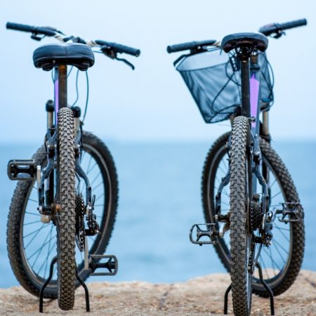 Two bicycles standing on the concrete pier on the blue water background